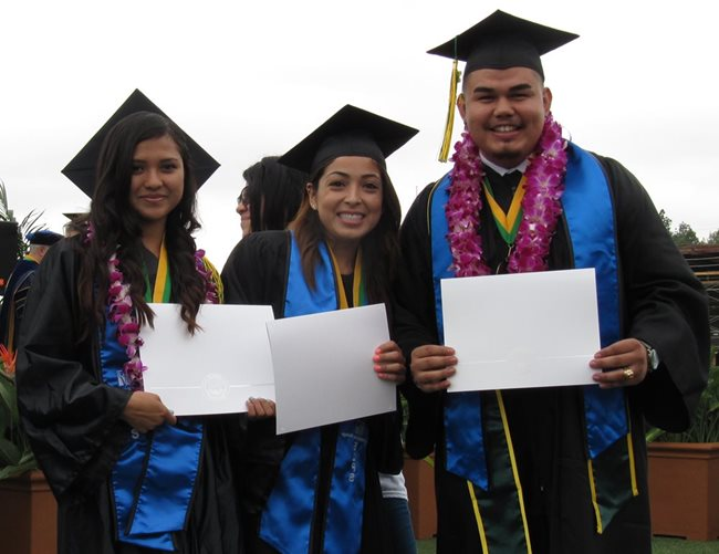 Two female and one male EOPS participants in cap and gown
